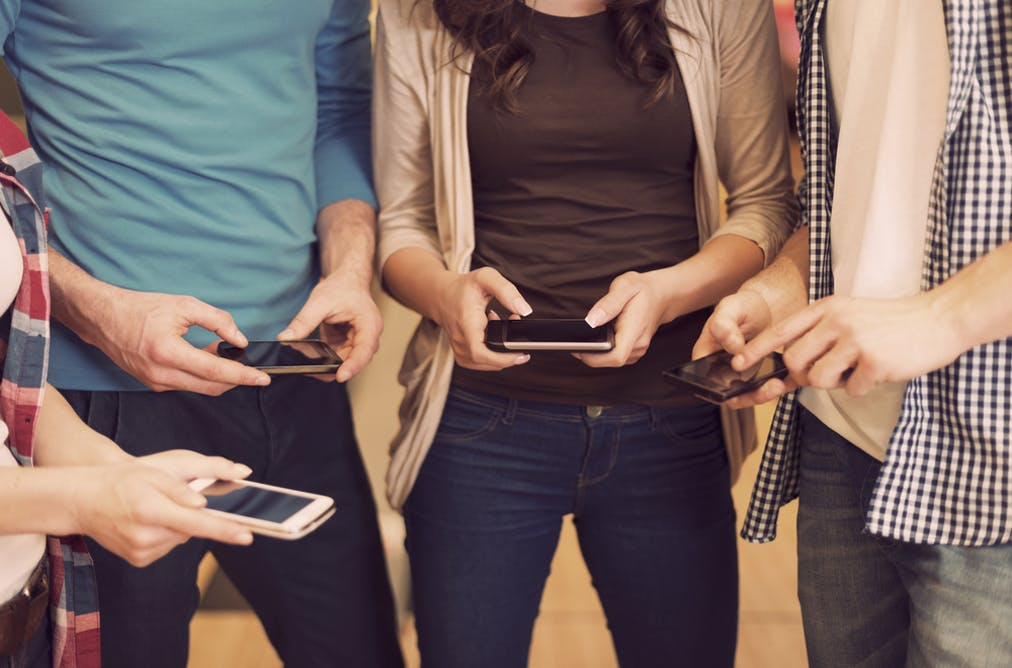 four people checking cell phones