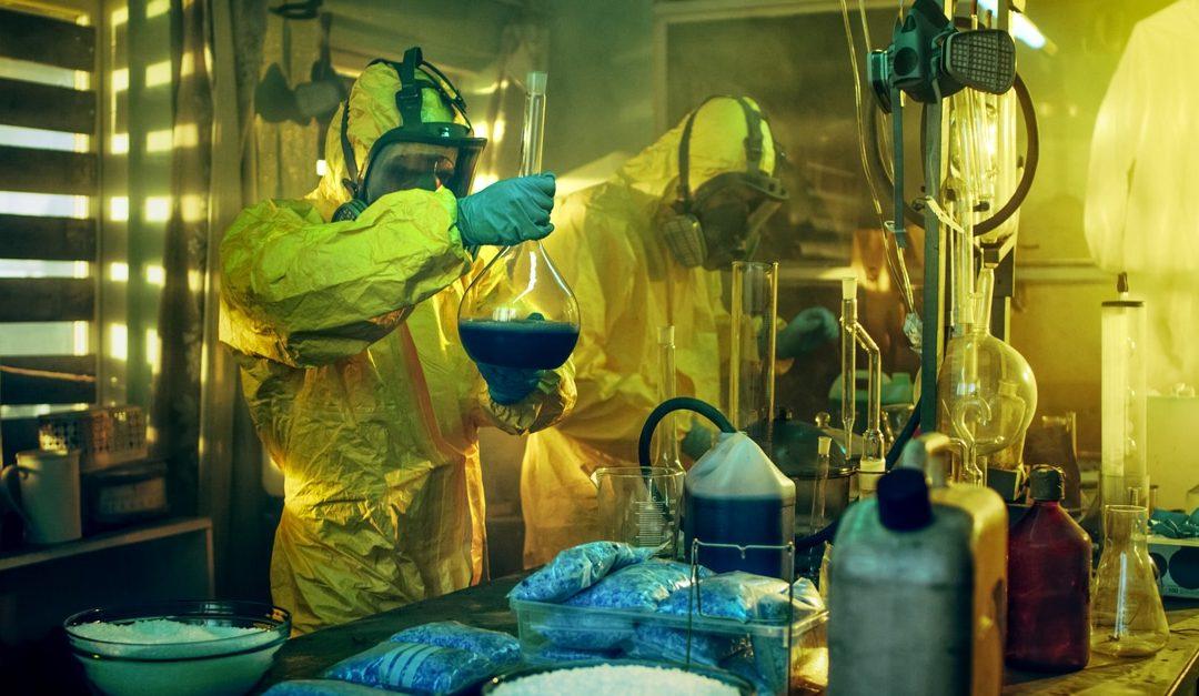 Two men in full hazmat suits in a Meth Lab